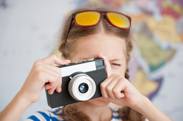 funny little girl with sunglasses on her hair taking picture with vintage camera