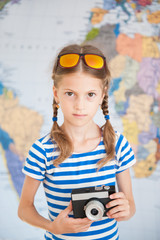 pretty small girl in sunglasses on her head with camera in hands on map backdrop