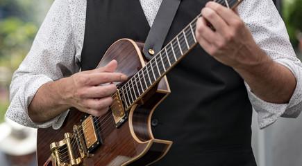 Chitarrista che suona chitarra con cromature, in concerto pubblico
