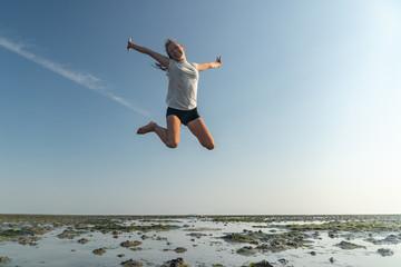 junges Mädchen springt im Wattenmeer der Nordsee vor Freude in die Luft