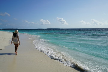 Young woman walking along the beach in the Maldives