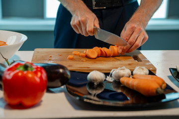 A man is cooking food, on a wooden board he cuts carrots
