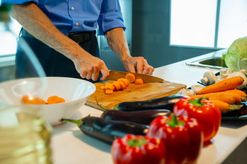 A man on a board cuts carrots