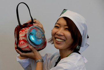 Japanese graphic designer Tanago Akiko demonstrates her creation, the prototype of Fan-Handbag during the Underground Maker Festival in Tokyo