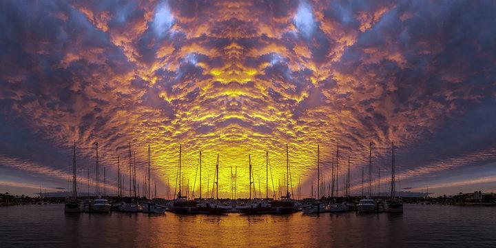 Orange colored altocumulus cloud, sunset seascape over marina.