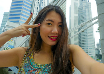lifestyle portrait of young beautiful and happy Asian Chinese tourist woman taking selfie photo with mobile phone smiling cheerful having fun