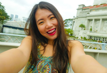 lifestyle portrait of young beautiful and happy Asian Korean tourist woman taking selfie photo with mobile phone smiling cheerful having fun