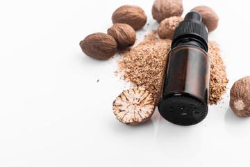 Fototapeta nutmeg essential oil on a white acrylic background obraz