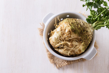Top view image of celeriac root on white wooden background