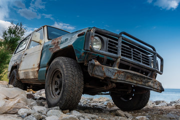 Poster Motorise The old rugged off-road vehicle stuck in a rocky terrain