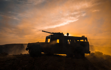 Military patrol car on sunset background. Army war concept. Silhouette of armored vehicle with gun in action. Decorated.