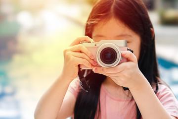 Asian Child Holding Camera Taking Photo Illustrating Travelling Concept