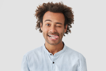 Positive attractive African American male with positive expression, shows tongue, has happy expression, stands against white wall, has crisp hair, have fun together with friends. Funny hipster