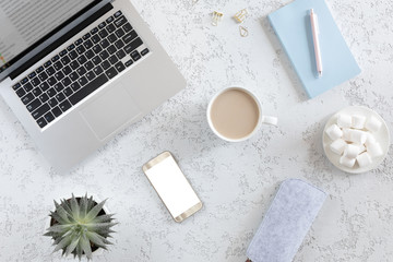 Top view of modern white office table with laptop, mobile phone, coffee cup, notebook, marshmallows and cup of latte coffee . Minimalistic flat lay, home office desk workspace
