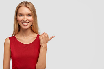 Horizontal shot of pretty happy slim woman has gentle smile, appealing look, points with thumb aside, dressed in red t shirt, happy to meet with talented musician at party. Advertisement concept