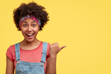 Horizontal shot of joyful curly dark skinned African American female with overjoyed expression, points aside against yellow background, dressed in fashionable dungarees, advertises someth