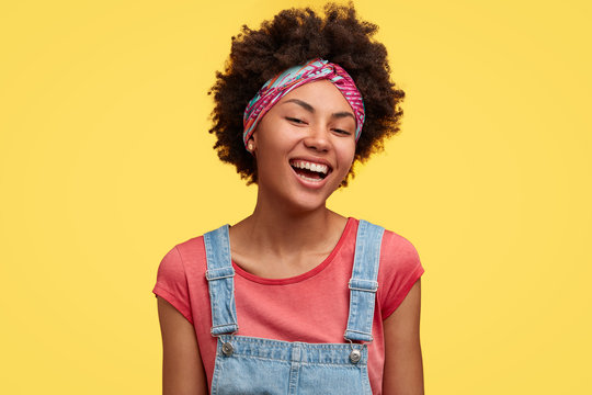 Happy young dark skinned female with Afro hairstyle, dressed in casual outfit, rejoices finishing household duties, has toothy smile, isolated over yellow background. Positive emotions concept