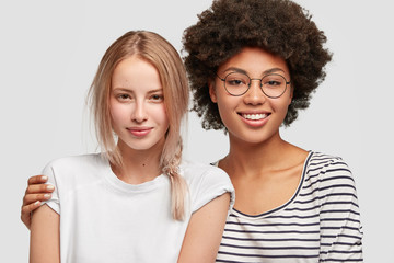 Sweet tender homosexual mixed race female couple hug and have friendly expressions. Lovely African American woman holds tight her charming best friend. People, emotions and friendship concept