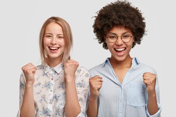 Horizontal shot of happy mixed race females clench fists with happiness, being satisfied with result of game, shout for their favourite team, have joyful expressions, isolated on white background