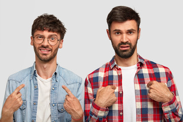 Displeased two young men indicate at themself, ask why they should do duties about house, frown face in discontent, wear stylsh shirts, have dark stubbles, isolated over white studio background