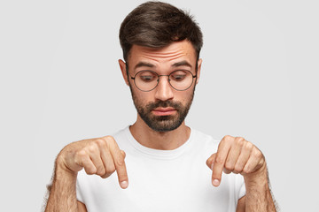 Headshot of handsome bearded male points down with surprised look, notices something on floor, wears glasses, dressed in casual t shirt, isolated over white background. People and astonishment