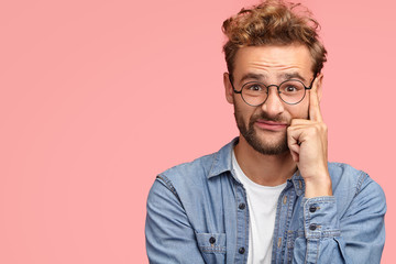 Fashionable male has curly hair and stubble touches temples and looks with seriousness, has puzzled facial expression, dressed in stylish denim shirt, poses over pink background with copy space aside