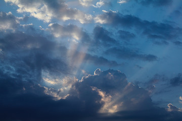 Summer sky with dark blue clouds and sun beams