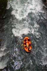 Un canoë rouge avec six personnes dedans va dans les rapides