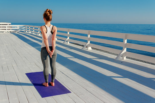 Young slim woman stretching outdoors at white wooden seafront. Girl standing on violet yoga mat with hands back in mudra. Exercise for shoulder blades