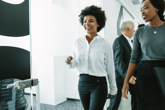 Woman with colleagues walking through office corridor