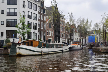 The canal of the river in Amsterdam, view from the water to the houses and the streets