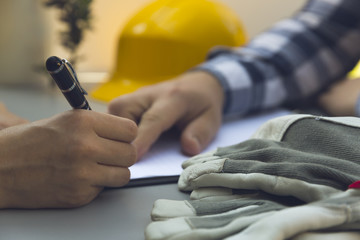 Woman signing construction contract with contractor. Yellow helmet, hard hat and gloves on grey table