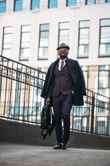 dark skinned experienced businessman leaving the workplace. full length portrait