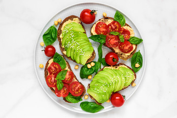 Avocado and tomatoes toasts with hummus, sesame and basil in a plate over white marble background. vegan food