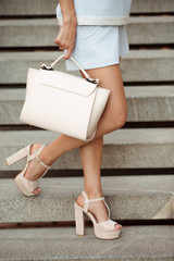 Cropped shot of woman in high shoes holding ivory bag