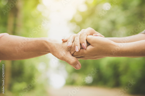 close-up of a daughter holding her mother's hand outdoors over nature background