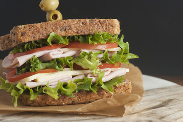 Double sandwich with ham, cheese, lettuce, tomato and green olives. Whole grain bread. Snack or take away food. Black background.