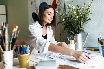 Young painter sitting at the desk with pictures dreamily working at cozy home