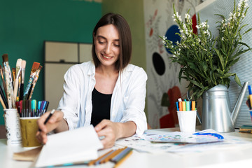 Smiling girl with dark hair sitting at the desk with paintings while happily drawing at cozy home