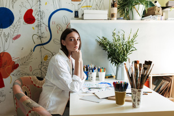 Young painter in shirt at the desk with pictures thoughtfully looking in camera in creative workplace at home