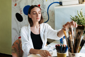 Young painter at the desk thoughtfully choosing paint brush in workplace at home