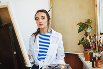 Beautiful girl in white shirt and striped T-shirt dreamily looking in camera while drawing on easel with paint tools near on window sill at home