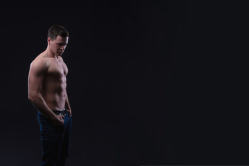 Handsome male fitness model showing naked torso, muscular body. Strong hands, chest and shoulder muscles and biceps. Studio shot on black background