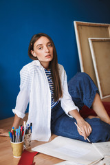 Pensive painter in white shirt and striped T-shirt sitting on floor holding pencil in hand while thoughtfully looking in camera with canvases on background at home