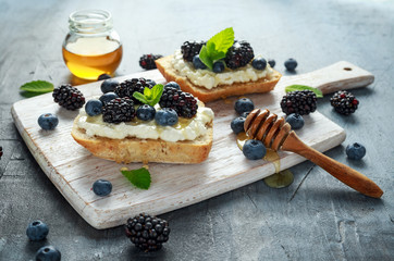 Fresh sweet Blackberry, Blueberry bruschetta, toast with cottage cheese, honey in a white board.