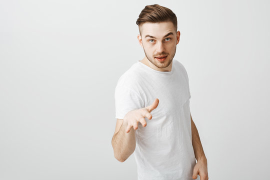 Listen to me. Mysterious handsome and stylish male coworker in white t-shirt pointing with palm at camera bending towards having suggestion or offer giving directions to employees over gray wall