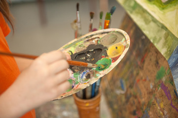 Closeup of paintbrush in kid`s hands mixing paints on palette