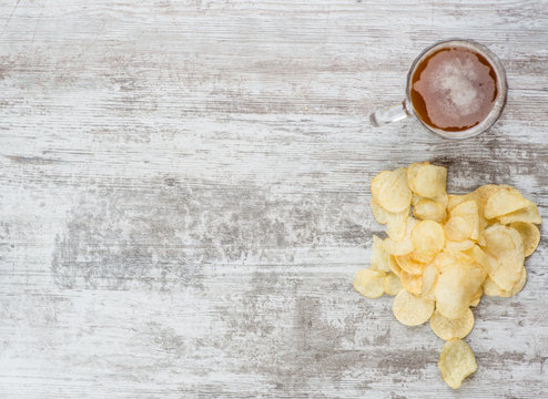 Top view mug of beer with chips