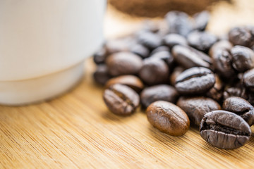 macro of coffee beans with cup on wooden board
