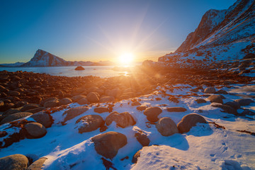 Landscape with beautiful winter sunset and snowy boulders at Lofoten Islands in Northern Norway.